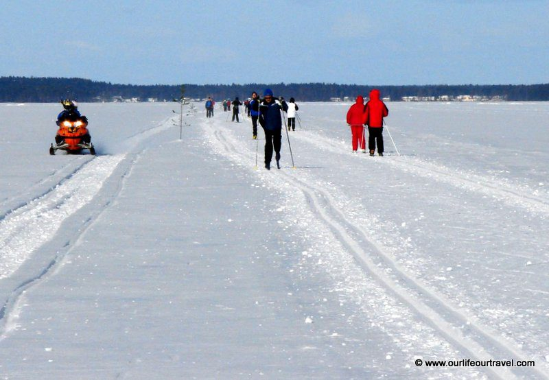 Cross-country skiing and a snow mobile on a lake in Finland